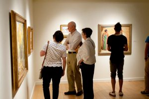 Three people look at a painting on the wall (unseen), while a man looks at a painting on the back wall.
